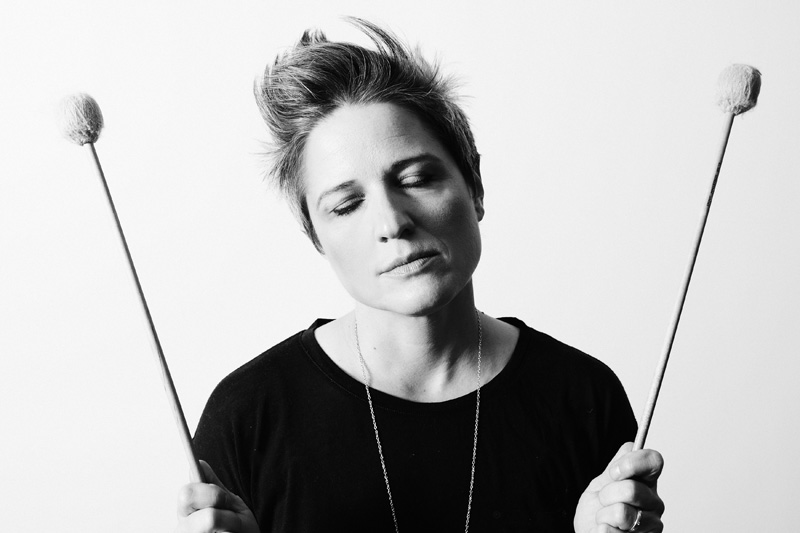 Allison Miller eyes closed, in dreamy way, holding percussion mallets.
